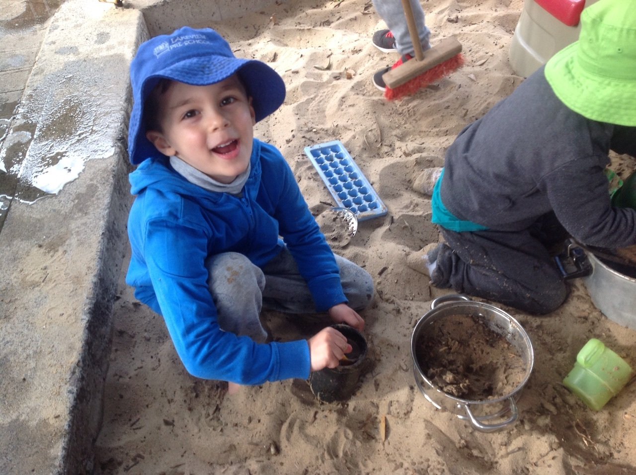 The sandpit is another big part of the outdoor curriculum, by Dominic's face you can tell that he is having lots of fun cooking with the sand.