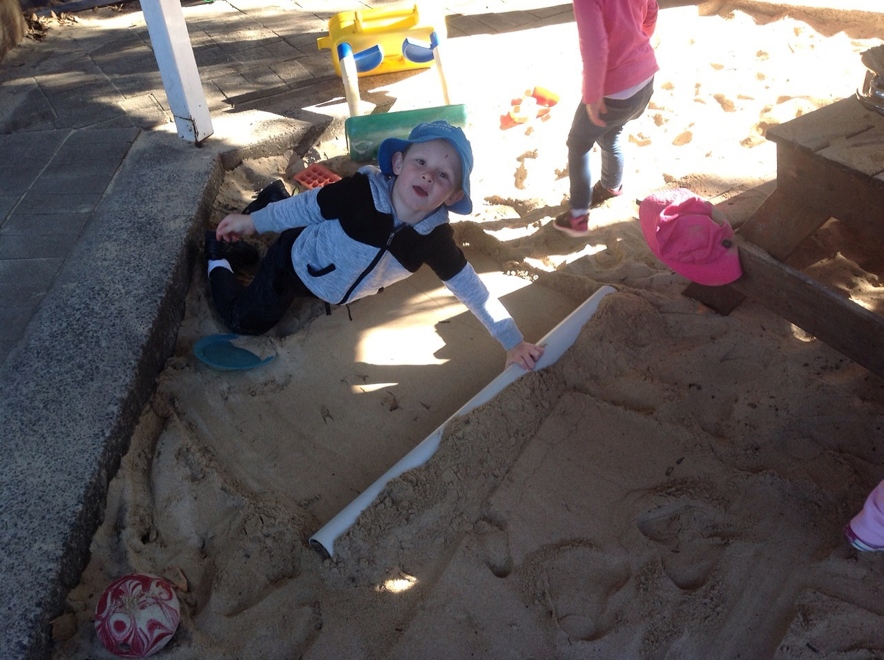 Brax used a pipe to roll out the sand in the sandpit.